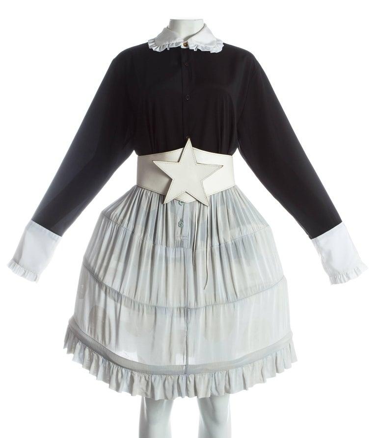 - polka dot print mini-crini skirt with ruffled hem  - white leather star belt  - black blouse with white ruffled collar and cuffs   Spring-Summer 1985