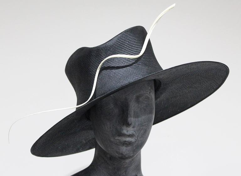A structured dress hat by Philip Treacy. The hat has a wide brim, a leather band, royal blue silk lining and a white straw motif. 