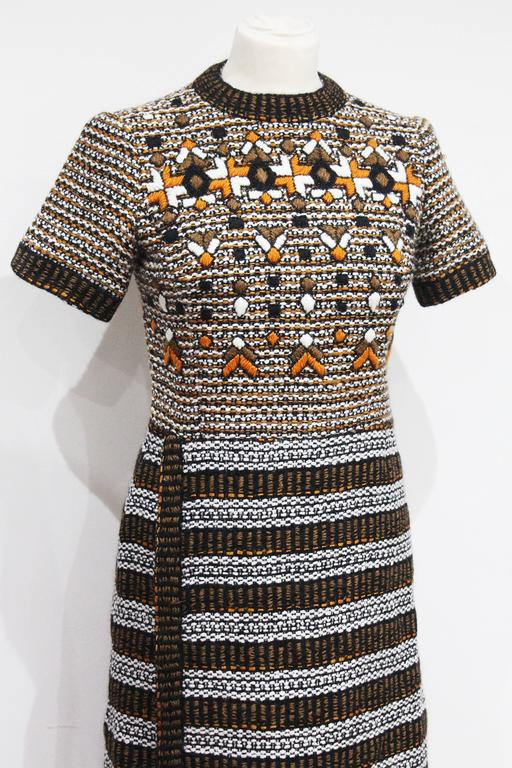 An exceptional 1960s French couture boucle embellished dress by Jacques Reval, Paris. The boucle has a vibrant and classic 1960s colour palette with orange, black and white in a fine wool. The bust is beaded in a geometric print. 