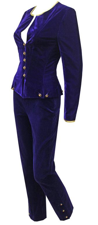 A fine and rare vintage Chanel velvet pant suit from the Autumn/Winter 1993 collection. The suit consists of a tailored velvet jacket with round neckline, long fitted sleeves, 5 gold 'CC' button closures running through centre, 4 sets of chain