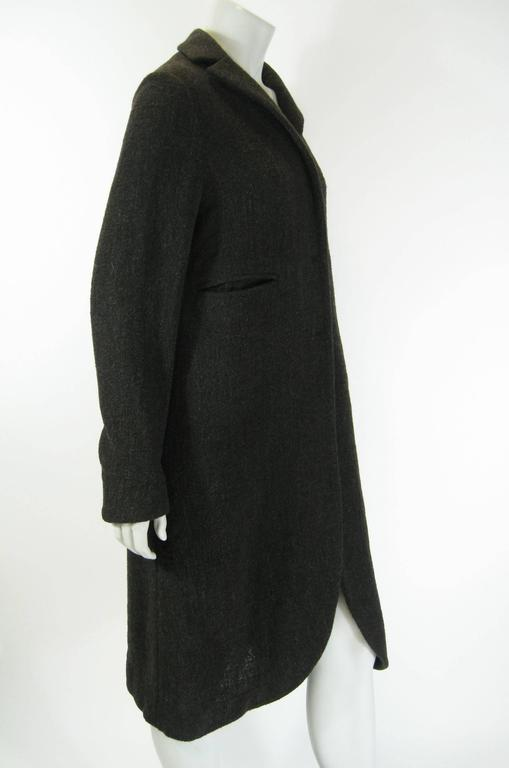 Marni long structured sweater coat. Dark gray/brown, aka taupe. Hidden button closure. Slit pockets. Slightly rounded peek-a boo hem. No lining. Tagged a size 42.  Bust: 40