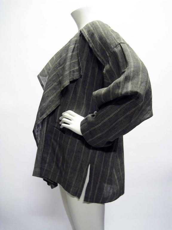 Early Miyake draped open jacket. Tagged men's size but unisex style. Gray linen with cream striped. Two front patch pockets. Back placket on shoulders. Tagged a size 9 (Japan).