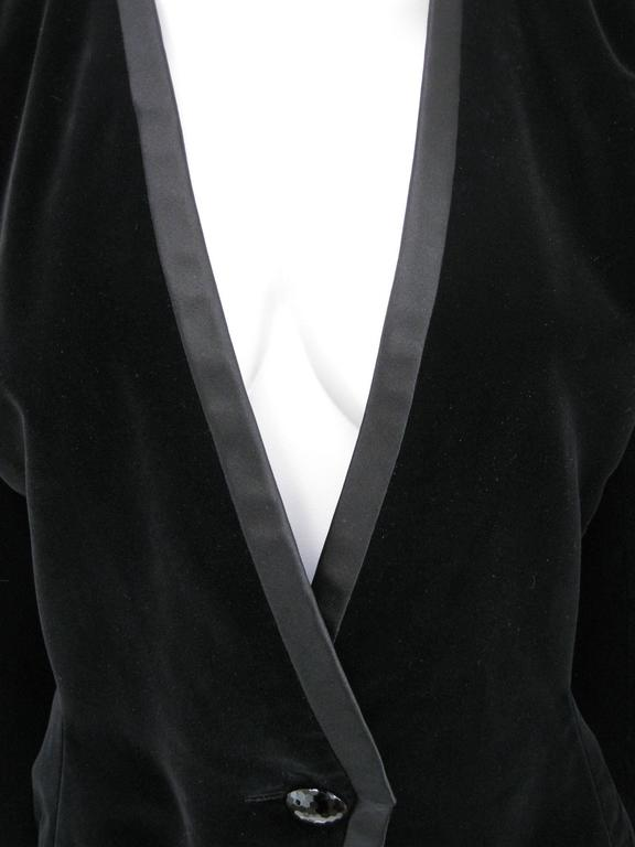 Luxurious YSL Rive Gauche evening jacket. Black velvet with silk satin trim. Fitted with faceted jet button closure. Trio of faceted jet buttons on wrists. Lined. Tagged size 42.