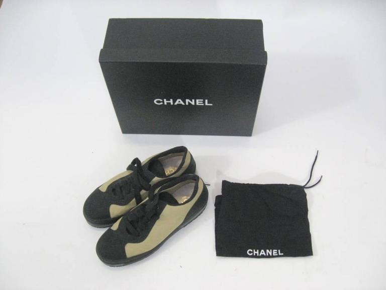 Authentic Chanel low top sneakers.  Off-white canvas & black nylon.  Black laces.  Padded tongue and heel.  Chanel stamp on heel.  Marked a size 39.  These come with the original box and dust bag.  These are in excellent condition,