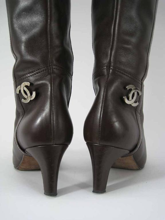 Chanel boots in brown leather with black accent at the toe box. There is a metal CC logo on the heel.   These are in good pre-owned condition, these do show signs of wear. Please note the wear on the front in the last photo.  These are made in