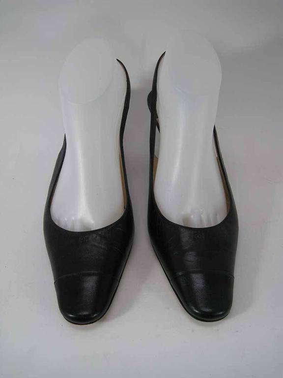 A pair of Chanel pumps in black leather with a small embroidered CC logo on the front upper.   These have been worn and show small signs of use. The leather is soft and slightly