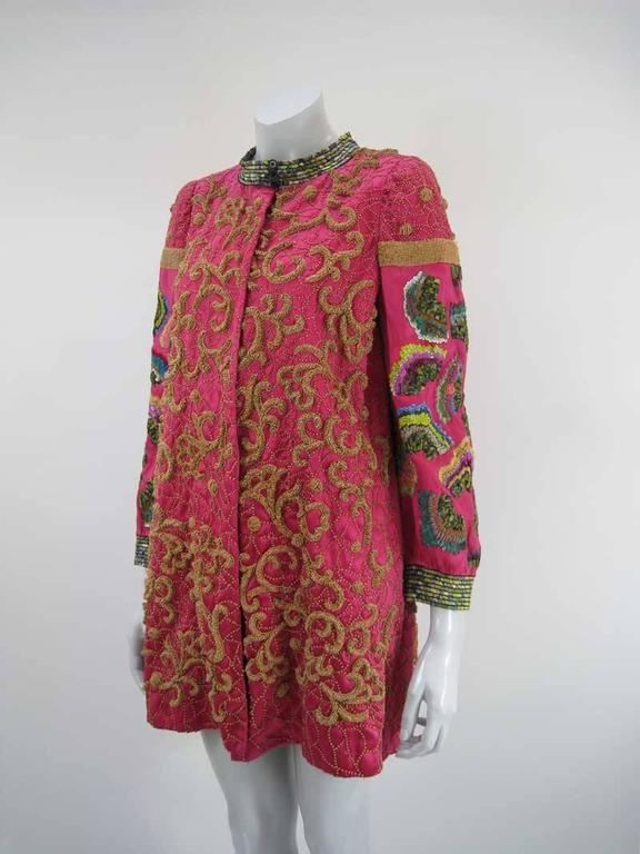 An extraordinary jacket from the Dries Van Noten Ready-to-Wear Fall 2008 collection.  Silk in a hot pink color with incredible embellishing.  Above the knee.  Silk, cotton and metal fibre.  Tagged a size 40.  This is in excellent pre-owned condition