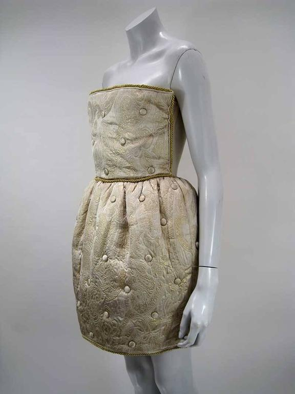 Outstanding gold Dolce & Gabbana quilted brocade dress.  Strapless with netted underlay and boning.  Gold cord trim.  Tufted skit that hits above knee.  Back zipper.  Skirt has satin lining.  Tagged a size 44.  Fabric of outer is polyester,