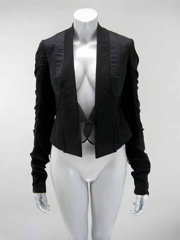 Black cropped avant garde Rick Owens jacket.  Detailed constructed with panels, pin tucking and tie embellishments.  Fitted cropped shape.  Extra long exaggerated sleeve.  Stretch ribbed knit underarm panel with silk ties along outer