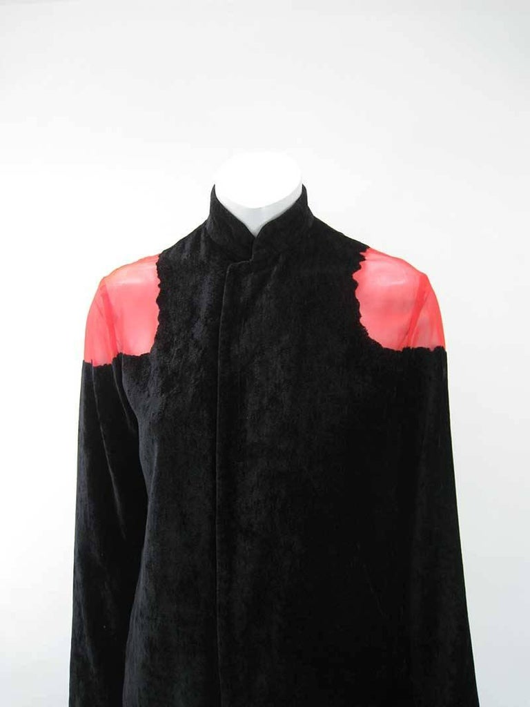 Stunning Yohji Yamamoto Noir crushed velour jacket with sheer red panel.  Soft lightweight black with undertones of red.   Jagged cut out shoulders and back.  Snap closure.  Made of polyester & rayon.  Tagged a size 2.  This is in excellent