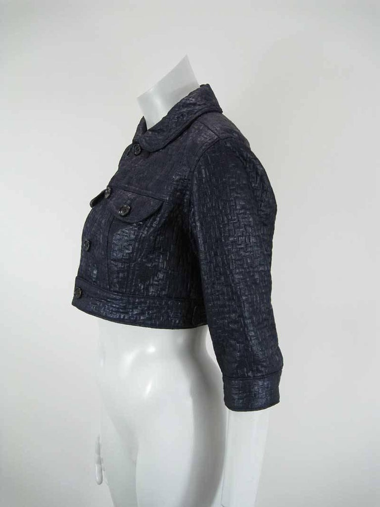 Deep navy blue Comme des Garcons cropped jacket.  Basket weave texture with sheen to fabric.  Cropped to hit at waist.  Button closure.  Front chest pockets.  Adjustable side tab closures.  Elbow sleeve with closure.  Tagged a size Medium.  Fabric