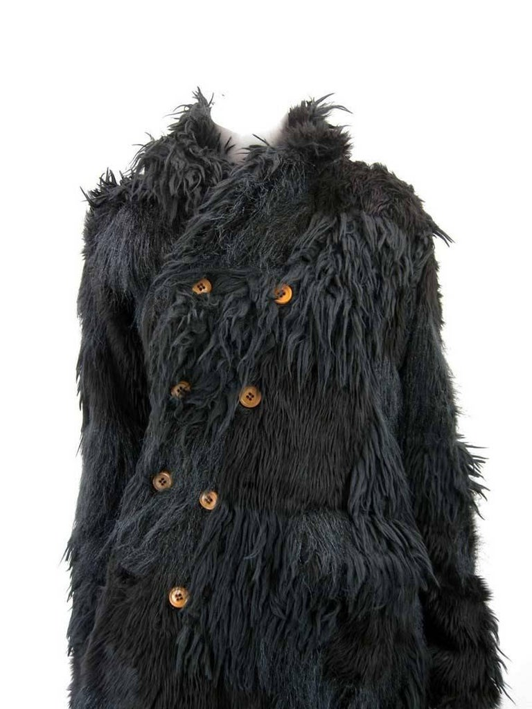 Fabulous coat from Comme des Garcon's 2002 AW Ready to wear collection.  This style of coat is currently featured at the MET Museum in NY.   Black faux fur coat in patchwork design.  Asymmetrical length.  Double asymmetrical wrap around