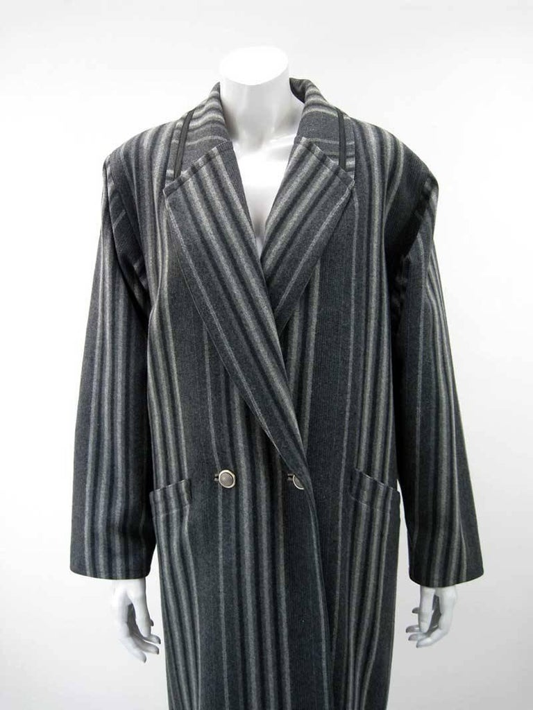 Handsome vintage Gianni Versace grey striped coat.  Oversize cut that narrows through hips.  Double-breasted with four two button closure.  Black ribbon trim on collar and back belt.  Front slant pockets on hip.  Wool with nylon lining.   This is in