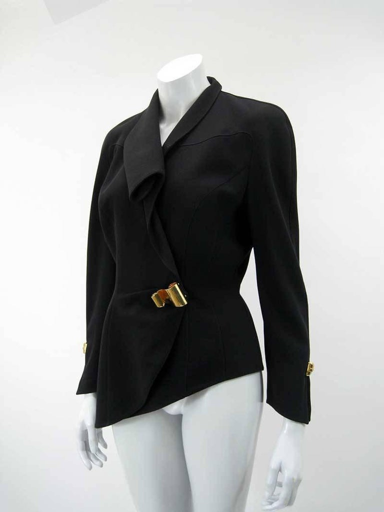 Stunning Thierry Mugler black asymmetrical blazer.  Fold over collar. Longer fitted shape with exaggerated shoulders.  Hidden snap closures with bright brass decorative scroll embellishments on front side and wrists.  Tagged size 38.  Fully lined.