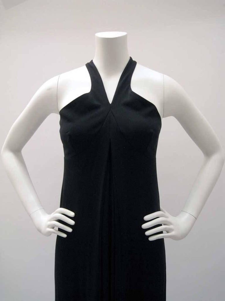 Classic Gianfranco Ferre long black dress.  Empire waist with open back and criss cross straps.  Inverted pleat with full skirt.  Back zipper.  No fabric content tag, jersey material with stretch.  No size tag.  This is in excellent pre-owned