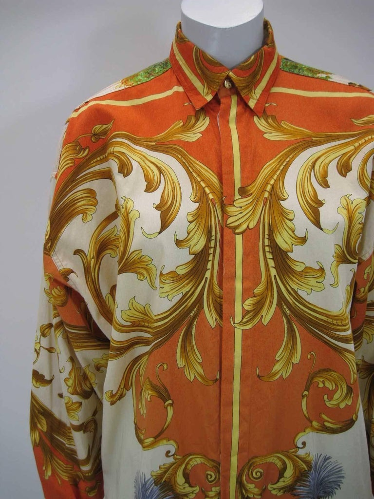 Striking Versus Gianni Versace button down shirt.  Baroque print of birds, bucks and a large goddess on the back.  Vibrant hues of burnt orange, yellow, gold and more.  Button down collar.  Hidden button placket.  Fabric is cotton.  Button