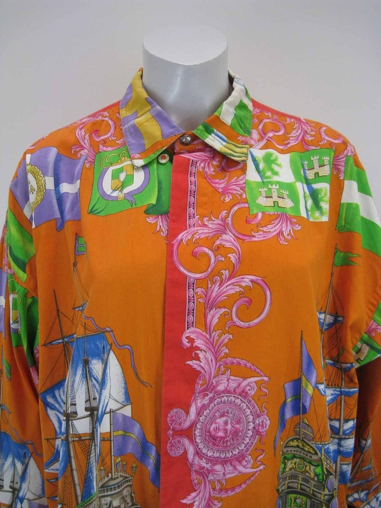 Striking Gianni Versace button down shirt.  Decorative print of sailboats, sun faces, flags and more.  Vibrant hues of orange, yellow, red, blue, green, pink and more.  Button down collar.  Hidden button placket.  Fabric is cotton.  Button