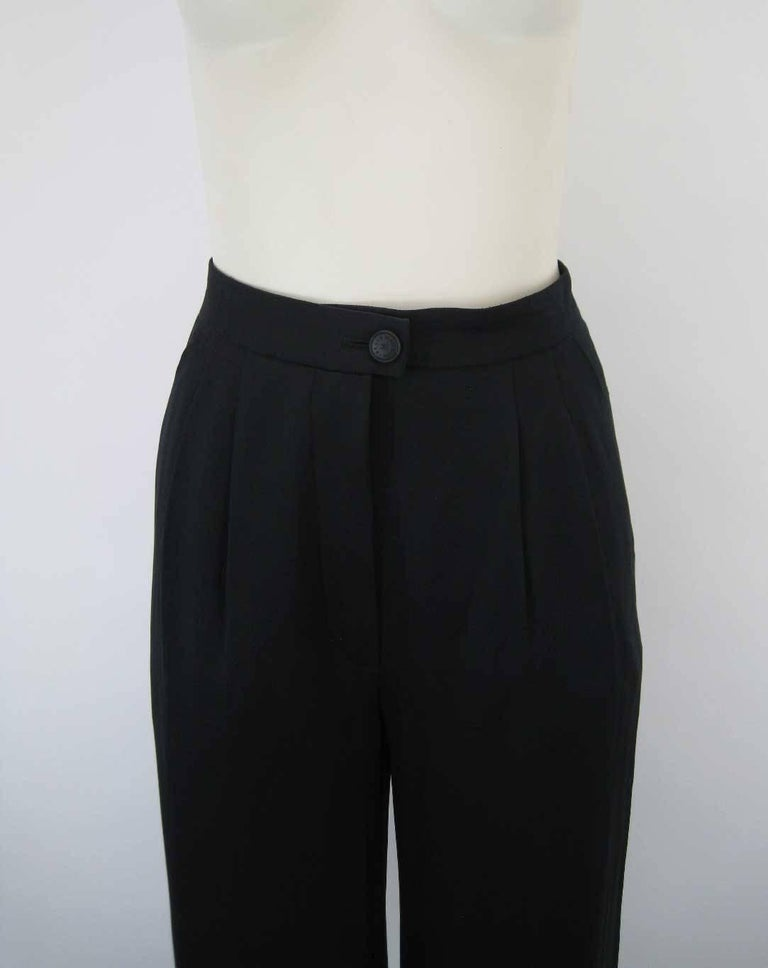 Elegant Chanel black silk cuffed pant.  Flattering cropped length.  Inverted double pleated waist.  Chanel embossed button closure with zipper.  Loose, wider leg with cuff.  Side pockets.  Fabric is silk.  No size tag.  This item is in excellent