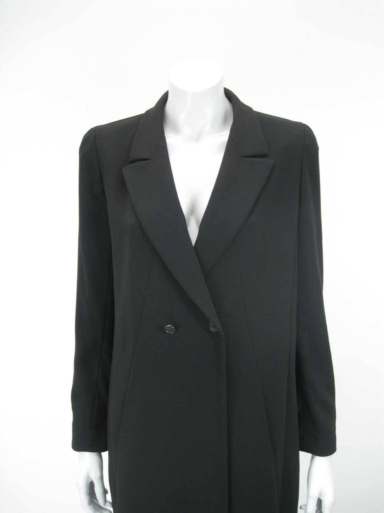 Elegant Chanel Boutique long black jacket. I believe the 98P denotes Printemps 98, or Spring 1998.  Suit tailoring with low neckline.  Double breasted with CC button closure and one hidden closure.  Flattering seaming with side pockets.  Fully lined