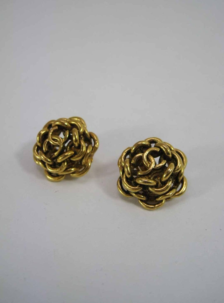 1980's Chanel gold tone interlocking CC earrings.  Round rows of interlocking chain with CC on top.  Clip-on style.   Stamped 222 Chanel on back.  This item is in excellent pre-owned vintage condition with minimal wear to metal.  MEASUREMENTS: 1