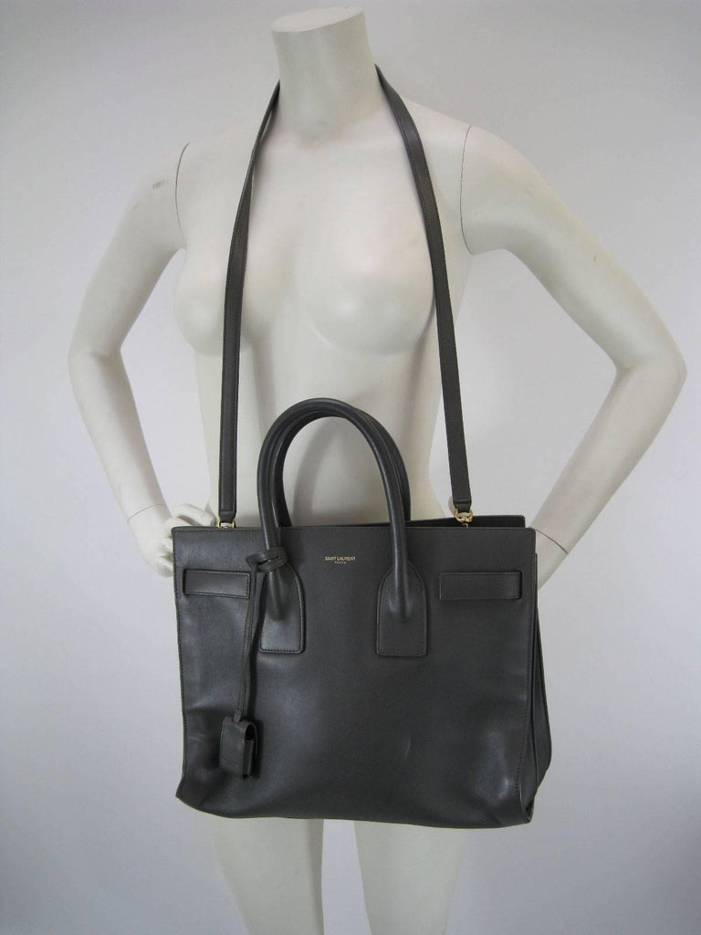 Signature Saint Laurent Sac de Jour bag in gray.  This classic bag features tubular handles, side gussets with compression tabs.  Long removable adjustable shoulder strap.  Saint Laurent embossing.  All brass hardware & brass feet.  100% Calfskin