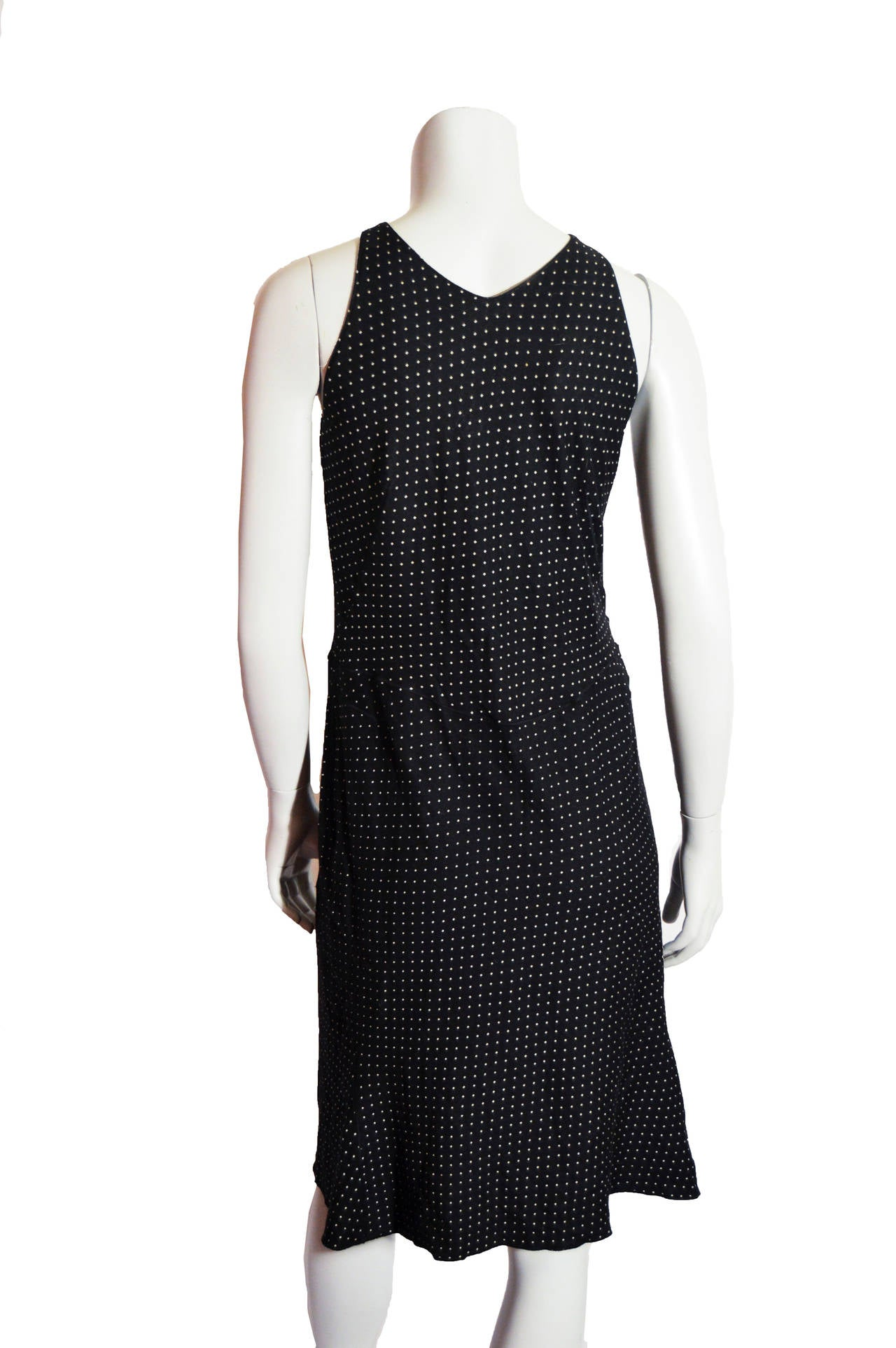 This Alaia dress is black wool and rayon with white polka dots. The dress is constructed with a size zip and shoulder hooks. The fluted skirt is longer in the back of the dress. The dress is tagged a size large.