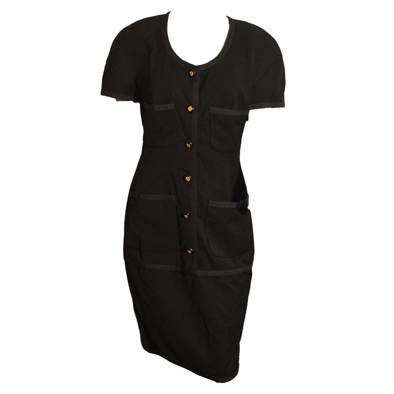 This black 1980's Chanel dress has a 6-button front and 4 pockets. It features ribbed piping, a drop waist skirt and black silk lining. The dress is tagged a size 42.