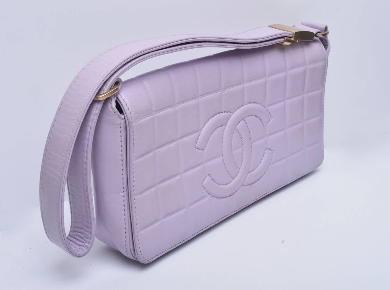 Gorgeous authentic Chanel quilted purse. Lovely muted lilac color. Leather. Gold hardware.  Adjustable shoulder strap. Stamped clasp. Refurbished by Chanel (receipt from Chanel included). Magnet closure.