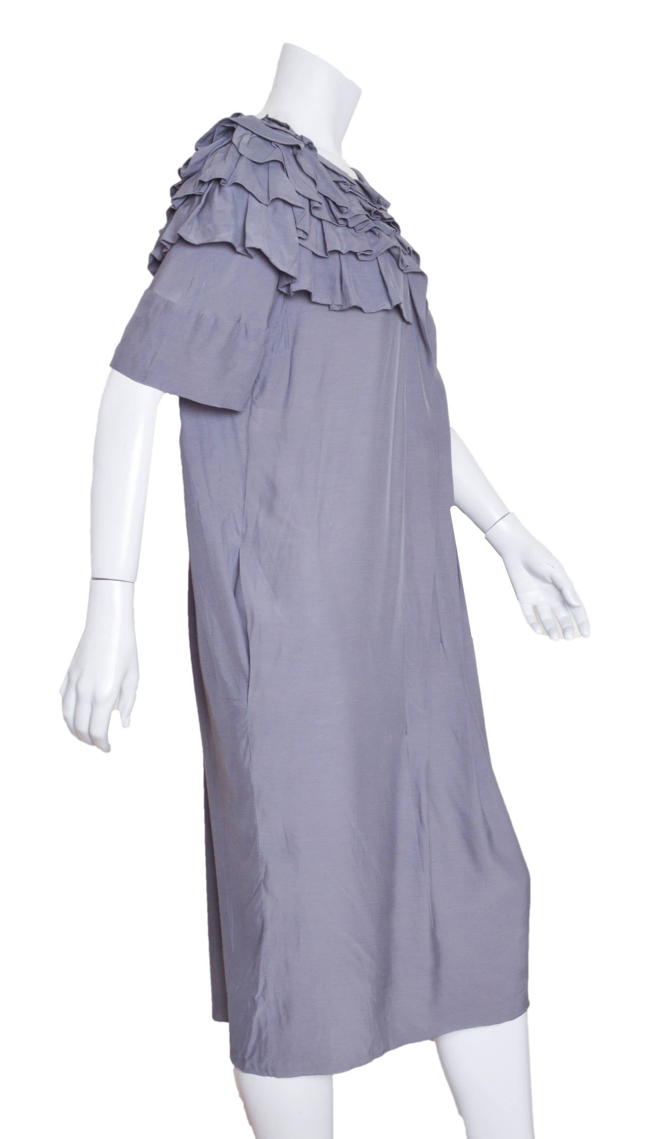 Innovative Marni gray dress. Beautifully folded fabric ruffles  that follow the neckline and wrap around back shoulder. Ruffles open into inverted pleats down the dress.  Exposed zipper in the back and hidden pockets. Tagged a size 42.