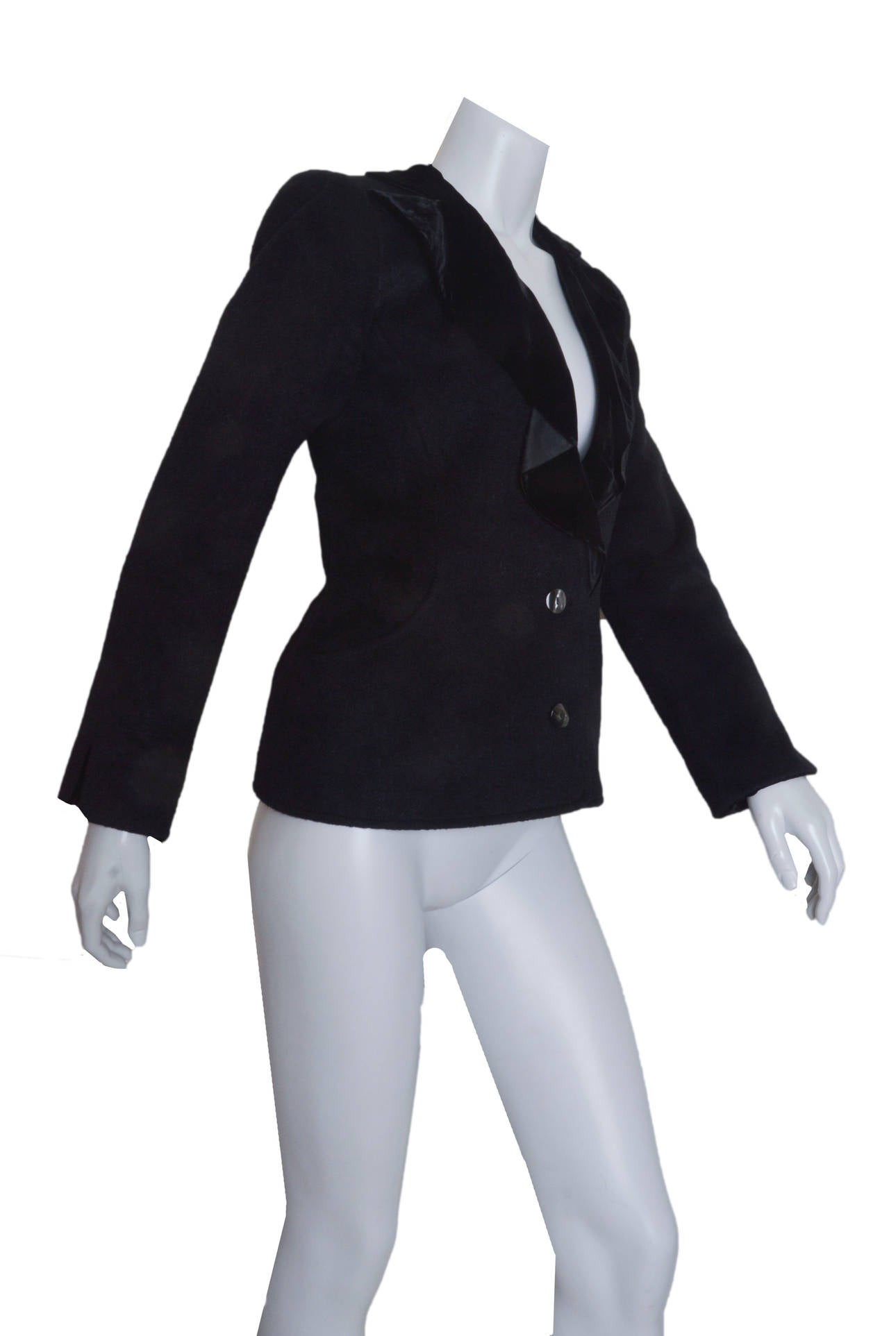 Classic YSL black tuxedo jacket. Wool with silk velvet lapels and cuffs. Fitted shape. Two button closures. Lightly padded shoulders. Two hip pockets with velvet lining. Lined. No size tag found.