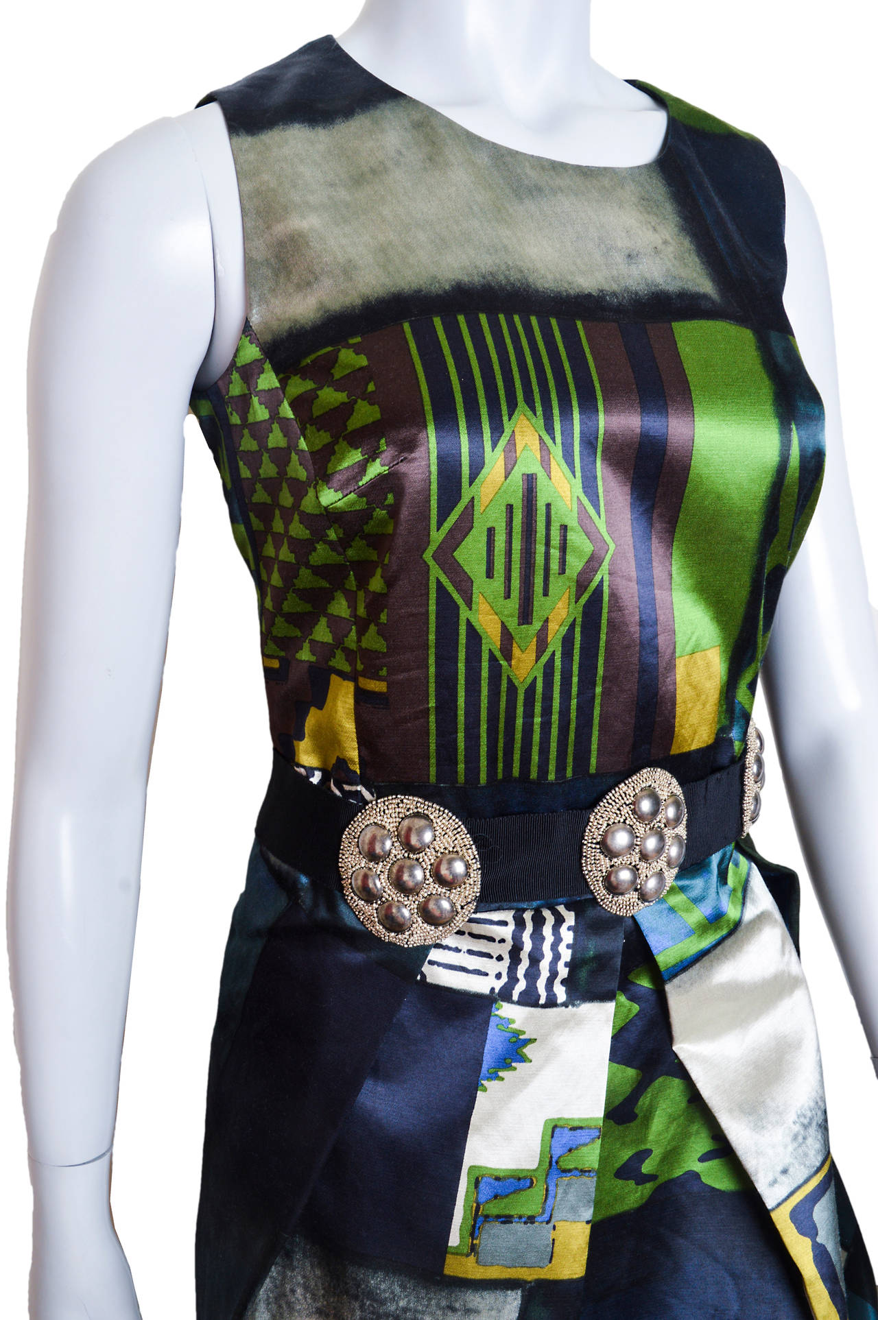 Subtle colors and a strong geometric pattern adorn this Etro dress. Semi sheen satin made of rayon/cotton blend. The centerpiece of this dress is the wide black self belt with three hand beaded embroidered silver medallions. Fitted hourglass