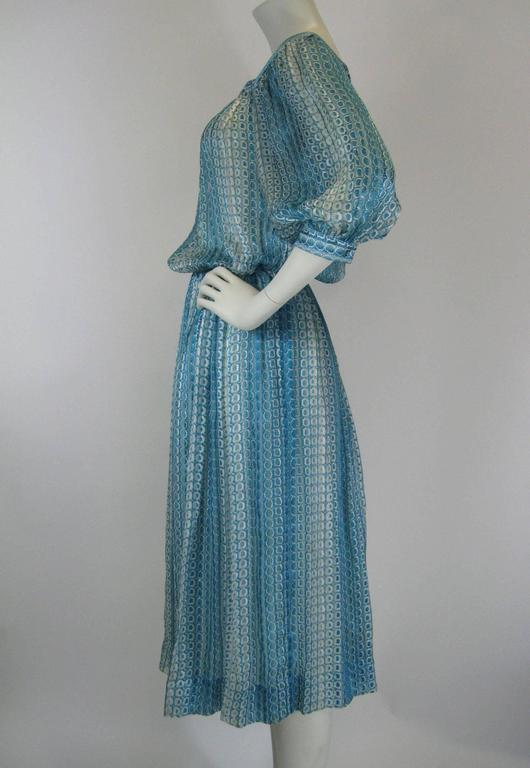 Stunning vintage Jean Patou silk printed dress. Lightest sheer silk chiffon. Vibrant turquoise and white vertical print. Square neckline, puff sleeves with closures at elbow. Side zipper on skirt, snaps on bodice. Full pleated skirt. Skirt is