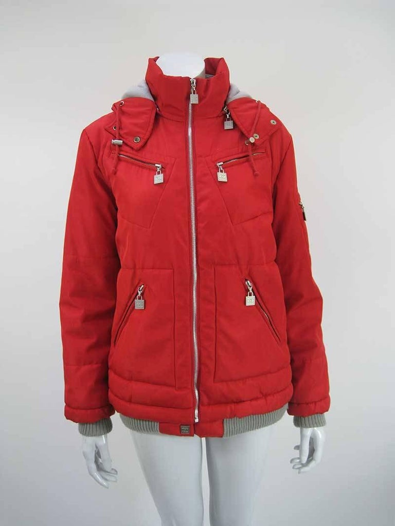 Vibrant red Chanel ski parka.  Full front zipper with silver hardware throughout.  Grey fleece lined inner neck and hood with double snap closure and cord.  CC zipper pull tabs on four front pockets.  Left arm pocket with CC patch.  Ribbed knit