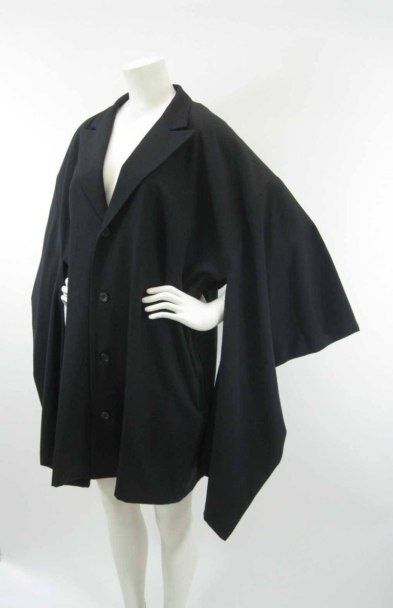 Black Yohji Yamamoto Japanese traditional with a twist style coat.  Boxy shape with long columns that hang from sleeve.  Fold over collar.  Four button closure.  Unlined.  Tagged size M. (This item is listed as unisex however it is sized a men's