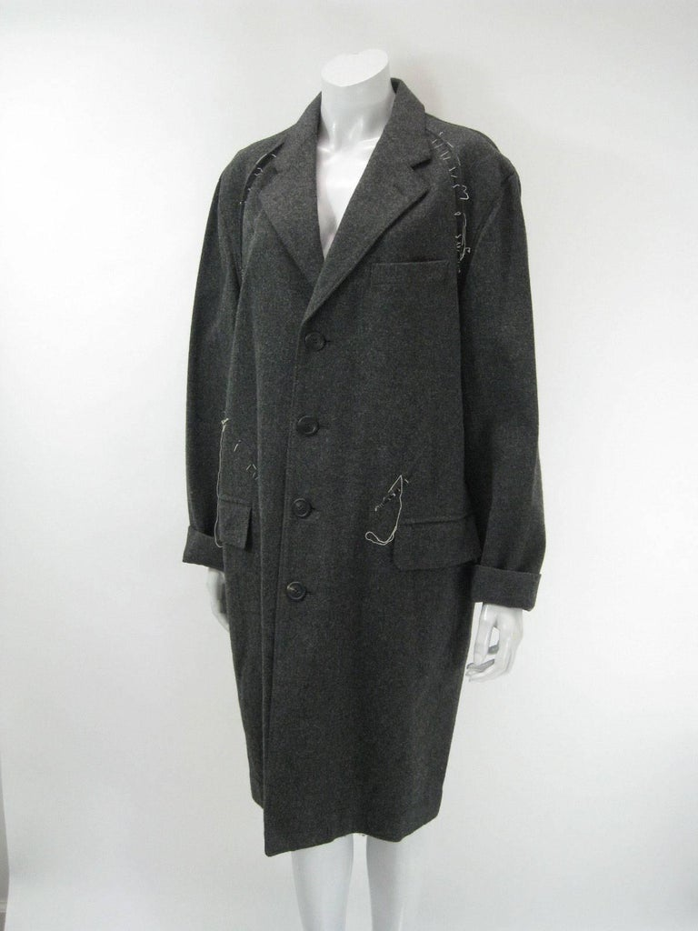 Avant Garde Issey Miyake Men wool coat.  Grey with white threaded abstract stitched details.  Front patch pockets. One chest pocket.  Inverted pleat back with pleats and stitches.  Large charcoal grey buttons.  Unlined.  Tagged size 3.  Fabric is