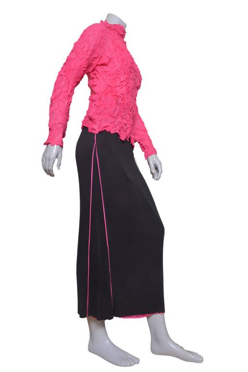Stunning Issey Miyake blouse and skirt set. Lightweight crinkled hot pink top with high neck and neck long sleeves. Pleated long black straight skirt with pink pipping and underskirt. Elastic waist. Tagged a size Medium.  Top