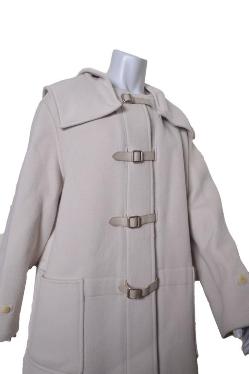 Lush Hermes coat. Color is a very pale gray/cream. Wool with cashmere. Detachable hood. Leather belt and buckle closures. Huge front bucket pockets. Shoulder amulets. Unlined. Tagged a size 44.