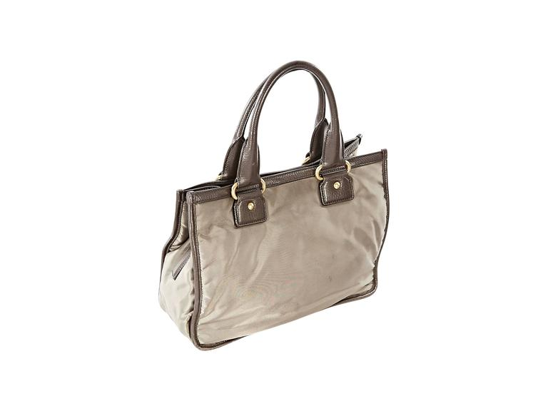 Taupe fabric tote bag by Prada.  Logo design accents front.  Trimmed with brown leather.  Tote carry handles.  Snap tab closure.  Lined interior with zip pockets.  Protective metal feet.  Goldtone hardware.  13