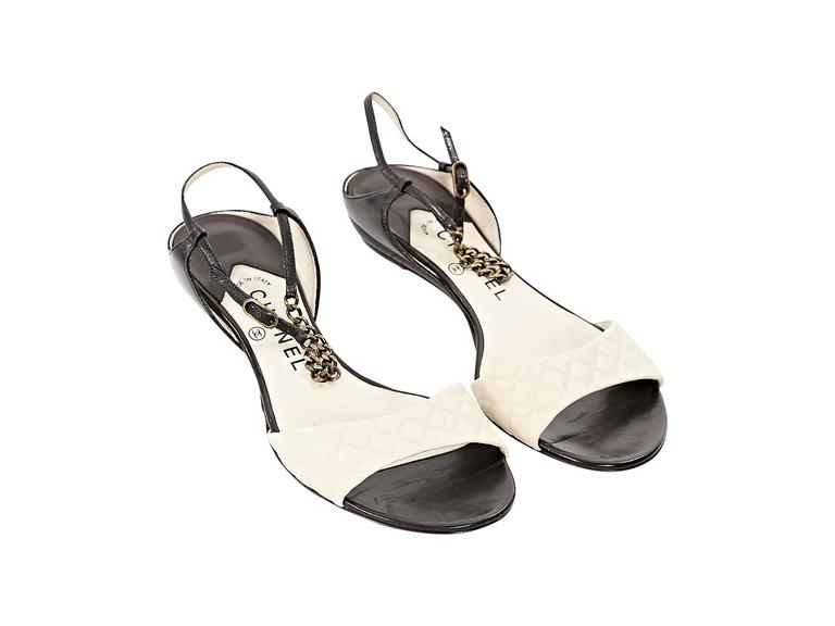 Product details:  Beige and black leather flat sandals by Chanel.  Adjustable ankle strap with chainlink.  Quilted vamp strap.  Open toe. Condition: Very good.