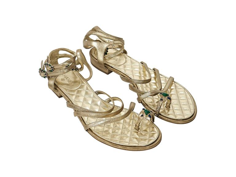 Product details: Gold leather strappy flat sandals by Chanel. Triple adjustable ankle straps. Embellished toe ring. Quilted leather lining. Condition: Very good.
