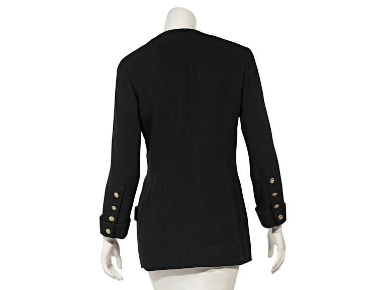 Product details: Vintage black corduroy jacket by Chanel. Scoopneck. Long sleeves. Turn back cuffs with four button detail. Double-breasted button front. Button flap front pockets.  Condition: Very good.