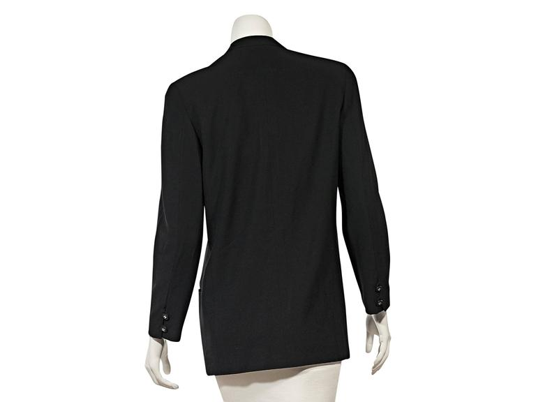 Product details: Vintage black jacket by Chanel. Crewneck. Long sleeves. Double button detail at cuffs. Button-front closure. Four besom front pockets. 