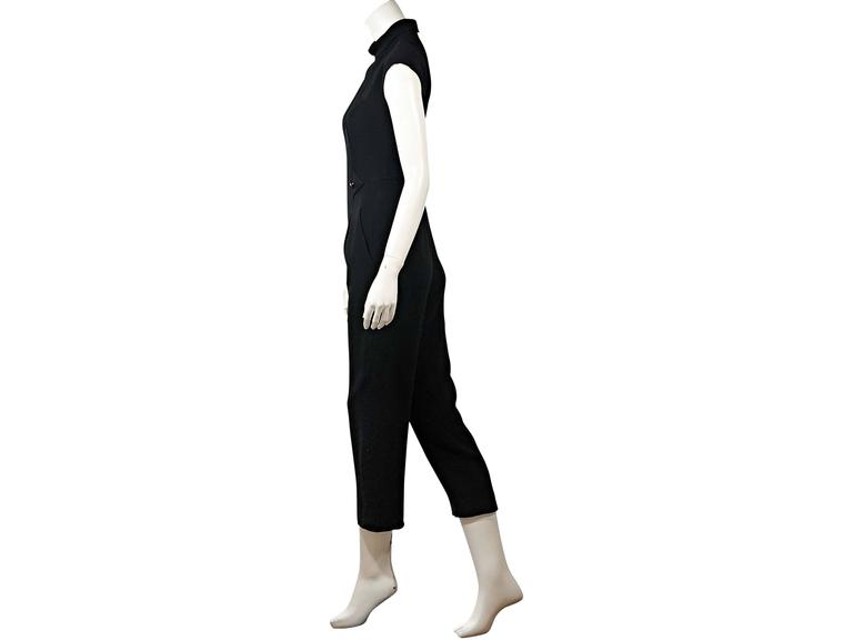 Product details:  Vintage black jumpsuit by Chanel.  Crewneck.  Cap sleeves.  Button accents.  Concealed back zip closure.     Condition: Very good.