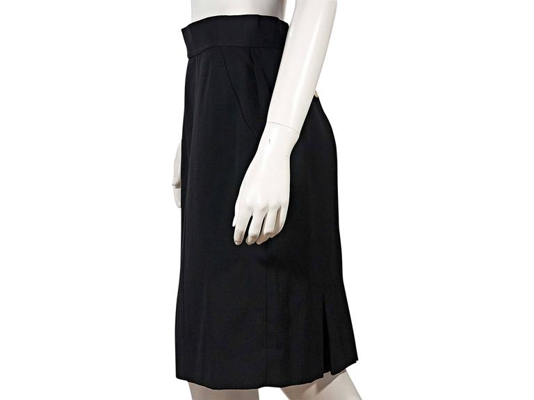 Product details:  Vintage black skirt by Chanel.  Banded waist.  Double button and concealed back zip closure.  Back besom button pockets.  Back inverted pleat hem vent.   Condition: Very good.