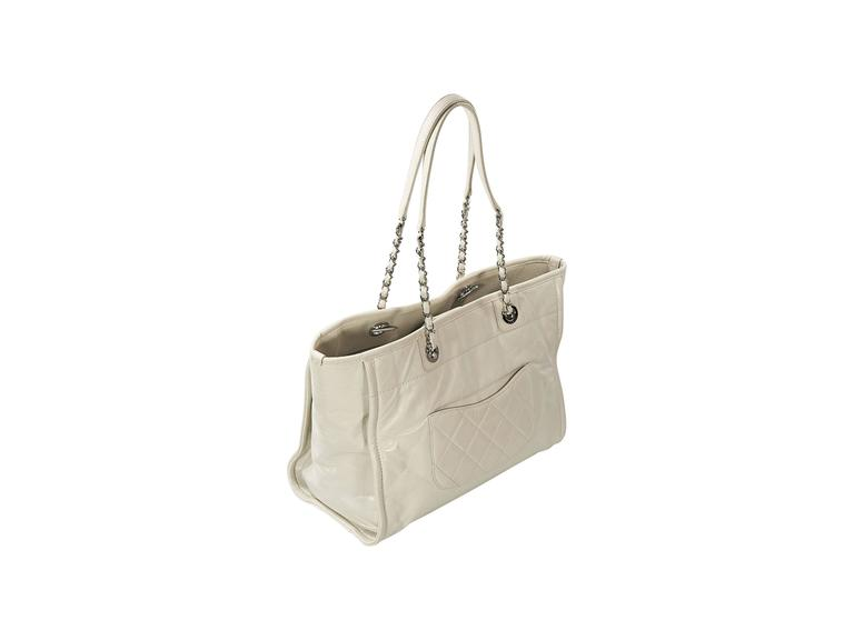 2fc27d462ccb Product details: White glazed leather Deauville tote bag by Chanel.  Embossed and embroidered logo