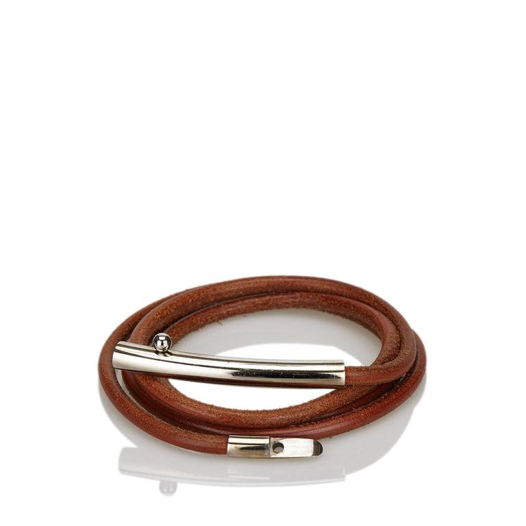 Product details:  Brown rolled leather belt by Hermès.  Clasp closure.  Silvertone hardware.  63