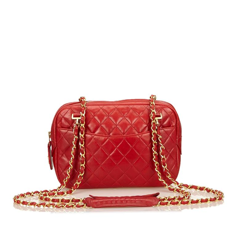 Product details:  Red quilted lambskin leather shoulder bag by Chanel.  Dual woven leather chain shoulder straps.  Top zip closure.  Lined interior with inner slide and zip pockets.  Front and back exterior slide pockets.  Goldtone hardware.