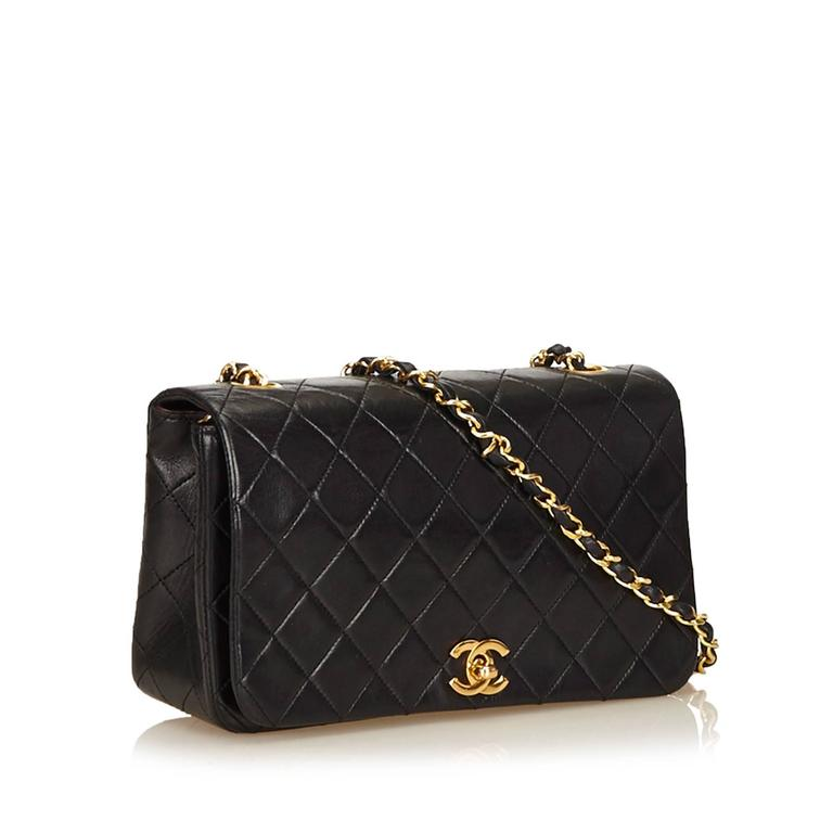 "Product details:  Black quilted lambskin leather shoulder bag by Chanel.  Leather woven chain shoulder strap.  Front flap.  CC twist-lock closure.  Leather lined interior with inner zip and slide pockets.  Goldtone hardware.  9""L x 5.5""H x 2.75""D."
