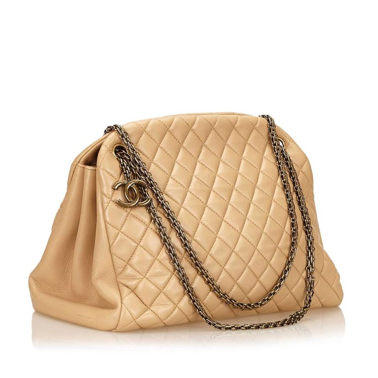 Product details:  Beige quilted leather Mademoiselle bowling bag by Chanel.  Dual chain shoulder straps.  Three main compartments- two open and center zip.  Lined interior with inner slide pockets and key fob.  Protective metal feet.  Antiqued