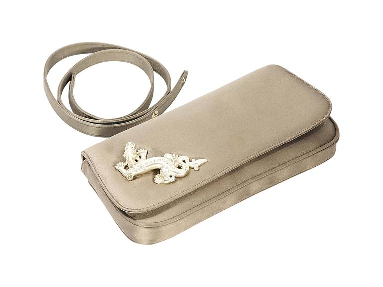 Product details: Bronze satin convertible clutch by Barry Kieselstein-Cord. Accented with a dragon charm. Detachable shoulder strap. Front flap with magnetic snap closure. Lined interior with inner slide pocket. Goldtone hardware. 9